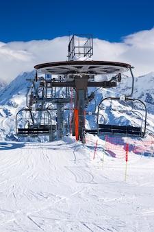 明るい冬の日のスキーリフトの椅子の垂直方向のビュー