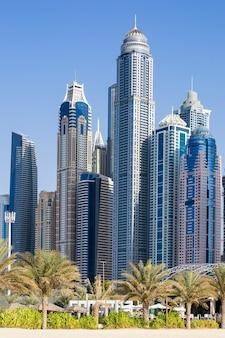 ドバイの高層ビルとヤシの木の垂直方向のビュー。アラブ首長国連邦