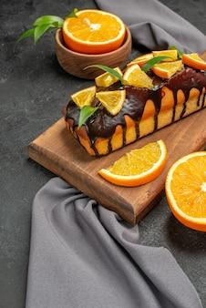 부드러운 맛있는 케이크의 세로보기는 나무 커팅 보드에 비스킷과 레몬을 잘라