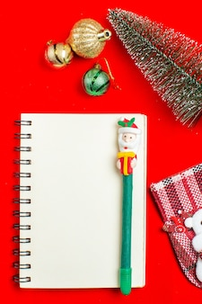 Вертикальный вид спиральной тетради с ручкой, аксессуары для украшения елки на красном фоне