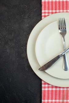 여유 공간이 있는 검정색 배경에 빨간색 벗겨진 수건에 흰색 빈 접시에 설정된 스테인리스 칼 붙이의 수직 보기