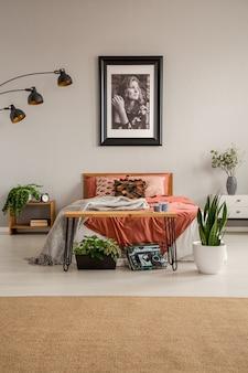 さび色の寝具、壁と緑の植物のポスター、実際の写真とキングサイズのベッドとスタイリッシュなベッドルームの垂直方向のビュー