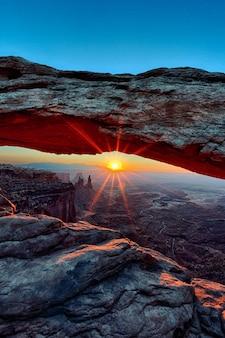 米国ユタ州キャニオンランズ国立公園のメサアーチの日の出の垂直方向のビュー