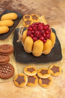 混合色の背景の茶色のプレートにおいしいケーキの異なるビスケットの垂直方向のビュー