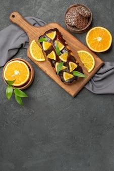 暗いテーブル映像のまな板にビスケットでおいしいケーキカットレモンの垂直方向のビュー