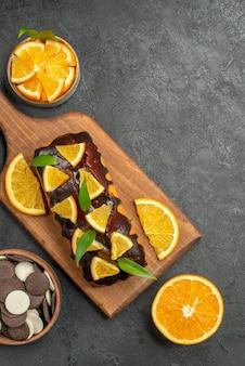 暗いテーブルのまな板の上にビスケットでレモンを切ったおいしいケーキの垂直方向のビュー