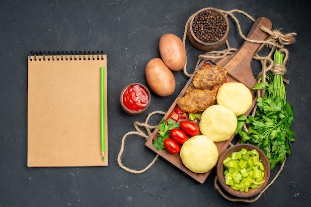 Вертикальный вид вкусных котлет нарезанных овощей пучок зелени на обед и тетрадь
