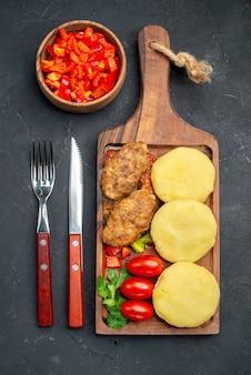 Вертикальный вид вкусных котлет, нарезанных овощей, зелени на ужин на темноте
