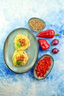 青い背景にパスタの食事と野菜と肉とおいしい夕食の垂直方向のビュー