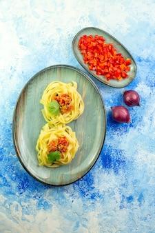 Вертикальный вид вкусного ужина с пастой и овощами на синем фоне