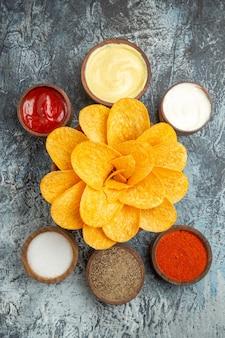 회색 배경에 케첩 마요네즈와 꽃 모양과 소금처럼 장식 된 맛있는 감자 칩의 세로보기