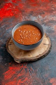 混合色のテーブルの茶色の木製トレイに青いボウルのトマトスープの垂直方向のビュー