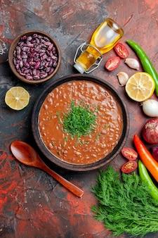 Вертикальный вид томатного супа, бутылки масла, фасоли, лимона и пучка зеленого на столе смешанных цветов