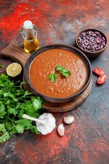 茶色のまな板の上のトマトスープと混合色のテーブルの上の緑の束の垂直方向のビュー