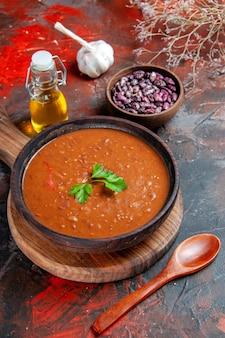 茶色のまな板の上のトマトスープと混合色のテーブルの上の豆の垂直方向のビュー