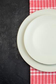 여유 공간이 있는 검정색 배경의 왼쪽에 있는 빨간색 벗겨진 수건에 있는 흰색 빈 접시의 세로 보기