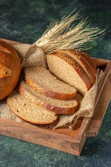 Вертикальный вид целого и нарезанного свежего черного хлеба на полотенце в коричневой деревянной коробке на поверхности темных цветов