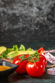 自由空間のあるミックスカラーの表面にカットされた新鮮な野菜とメータースパイス全体の垂直方向のビュー