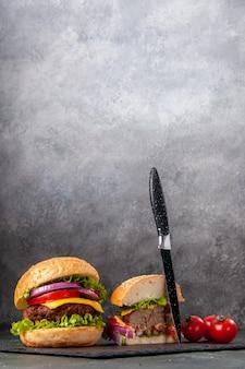 ダークミックスカラー表面の黒いトレイにステムナイフでカットされたおいしいサンドイッチとトマト全体の垂直方向のビュー