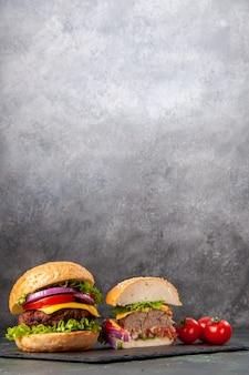 灰色のぼやけた表面の黒いトレイに茎を持つさまざまなおいしいサンドイッチとトマトをカットした全体の垂直図