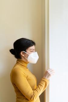保護マスクを着用して自宅で呼吸器の肺の問題を持つ女性の垂直方向のビュー。