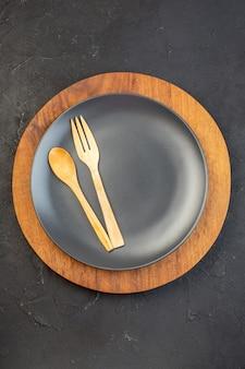 어두운 색 표면에 갈색 접시에 검정에 나무로되는 숟가락과 포크의 세로보기