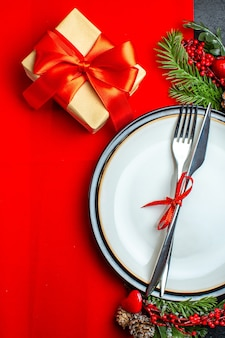 빨간 냅킨에 선물 옆에 디너 플레이트 장식 액세서리 전나무 가지에 빨간 리본으로 설정 칼 붙이 크리스마스 배경의 세로보기