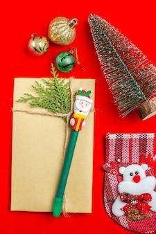 Вертикальный вид рождественского настроения с аксессуарами для украшения номеров рождественской елки на красном и черном фоне