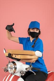 パステル ピーチの箱を保持している医療マスクと手袋を身に着けている自信を持って若い女性宅配便の垂直ビュー