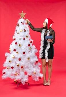 サンタクロースの帽子と新年のツリーを飾る黒いドレスを着た若い女性の垂直方向のビュー