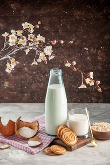 Vista verticale della bottiglia di vetro aperta e della tazza riempita con avena di biscotti con cucchiaio di latte in vaso marrone su asciugamano spogliato viola su tagliere di legno
