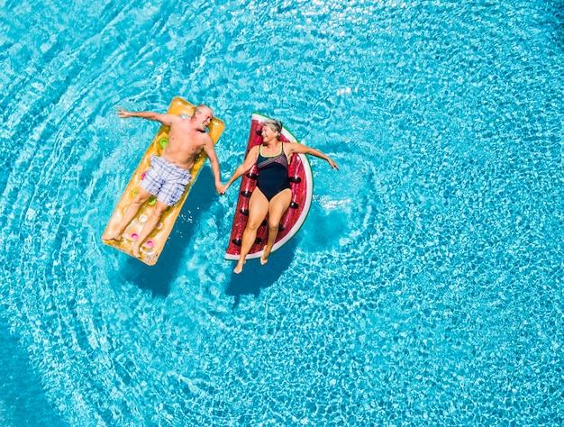 Above vertical view of people old senior couple taking hands with love and having fun on the blue clear swimming pool together enjoying the summer holiday vacation wth trendy lilos inflatable mattress
