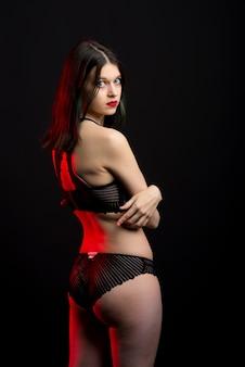 세로보기 사진 레이스 비키니 내실 브래지어 팬티에 아름 다운 수줍은 아가씨. 부드러운 마른 슬림 모양 격리 된 검은 공간.