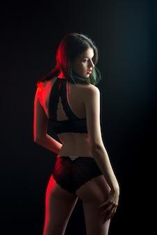 垂直ビュー写真レースビキニ私室ブラパンティーで美しい内気な女性。柔らかいスキニースリムな形状の黒い壁を分離