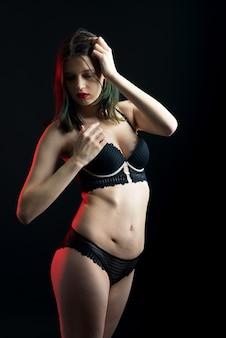 Vertical view photo beautiful shy lady in lace bikini boudoir bra panties. tender skinny slim shape isolated black wall