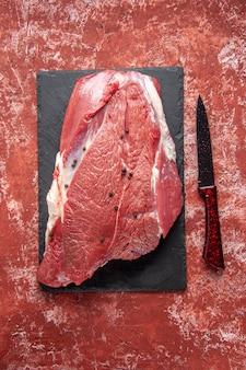 Vista verticale di carne rossa fresca cruda su tavola nera e coltello su fondo rosso pastello a olio con spazio libero