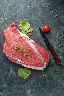 Vista verticale di carne rossa fresca cruda e verdure sul pomodoro del coltello del tagliere sul fondo nero verde di colori della miscela