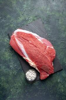 Vista verticale di carne rossa fresca cruda e sale sul tagliere su sfondo nero verde di colori misti