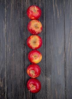 Vista verticale delle mele rosse su fondo di legno