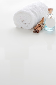 Vertical view of roll up of white towels and oil bottle on white table.