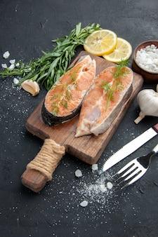 Pesce salmone vista verticale su tagliere di legno marrone con sale all'aglio verde e posate su sfondo scuro