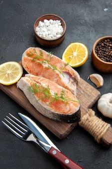 Vista verticale del pesce salmone su tagliere di legno marrone con fette di limone verde, peperoni sale, posate su tavola scura