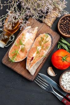 Vista verticale del pesce salmone sul tagliere di legno marrone con rami di abete al pepe verde e posate bottiglia di olio caduta pomodoro sale pepe sul tavolo scuro