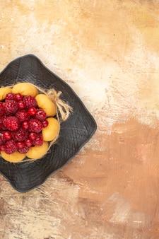 Vista verticale della tavola apparecchiata per caffè e l'ora del tè con lamponi su torte su tavola di colori misti