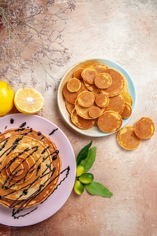 Vertical view of simple and decorated classic pancakes fruits on colourful