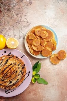 Vista verticale di frittelle classiche semplici e decorate su frutta colorata
