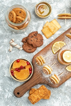 Vertical view of simple pancakes with lemons on cutting board and cookies honey on blue