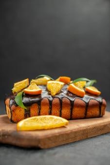 Vista verticale di torte morbide sul tagliere e limoni tagliati con foglie su sfondo scuro