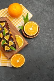 Vista verticale di torte morbide intere e tagliate i limoni con foglie sul tavolo scuro