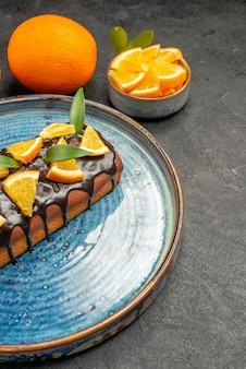 Vista verticale di morbida torta deliziosa sul vassoio e limone su sfondo nero